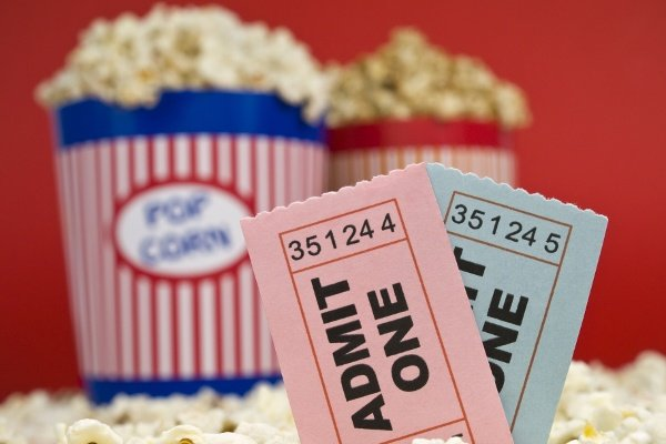 Movie Stub Two Sticking Out Of Popcorn With Two Pop Corn Bags In Background With Red Backdrop 1